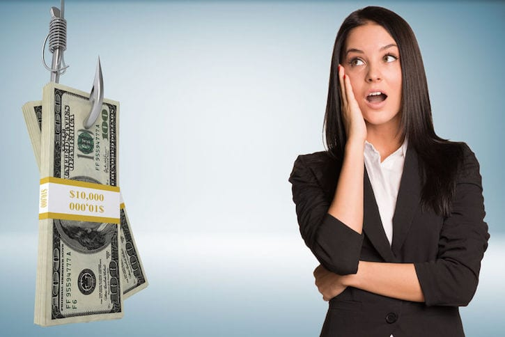42267947 - businesslady in suprise with open mouth and bundle of money on fish-hook on isolated grey background