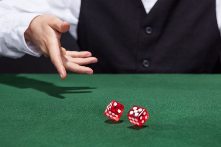 17389815 - croupier throwing a pair of red dice across the green felt on a card table in a casino in a game of chance