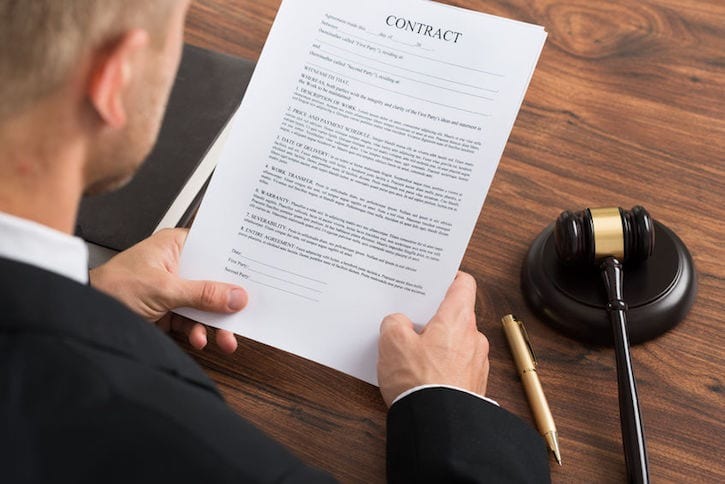 40245825 - close-up of judge reading contract paper at desk in courthouse