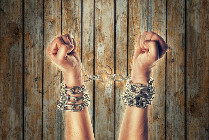 57119404 - two hands in chains on a wooden background background with scratches
