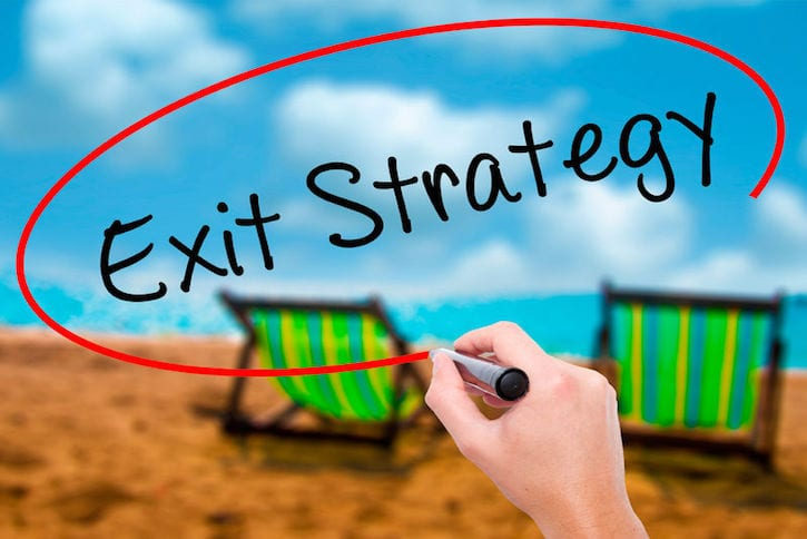 63510828 - man hand writing exit strategy with black marker on visual screen. isolated on sunbed on the beach. business, technology, internet concept. stock photo