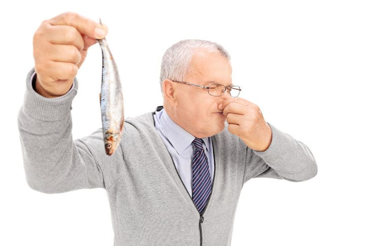 31619002 - senior gentleman holding a rotten fish isolated on white background